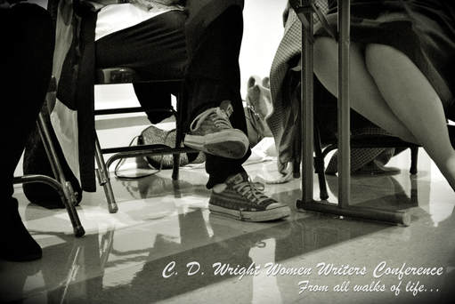 Black and white image of two sets of legs under a table. One pair in jeans and sneakers; one pair in skirt, hose, and pumps. Caption: C.D. Wright Women Writers Conference / From all walks of life...